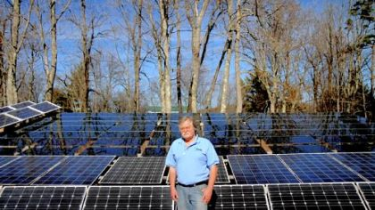 John Prusa, 57, director of innovation and technology for New Vision Renewable Energy, stands with the solar panels that have helped his Philippi, W.Va., home run on renewable energy.