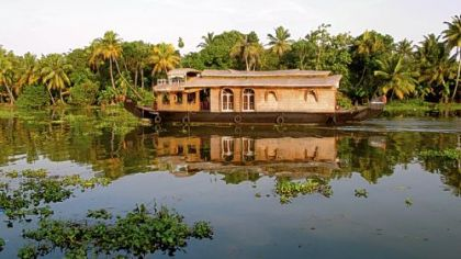A houseboat drifts along a canal in Kerala.