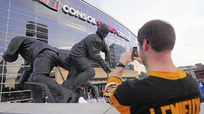 Brian Smith of Canonsburg takes a photo of his hockey idol's statue Wednesday before the Penguins game with Toronto.