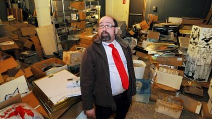 Joe Wos, executive director of the ToonSeum, Downtown, looks over comics, displays, books and other material damaged by a recent leak in the museum's North Side warehouse.