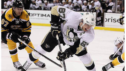 Sidney Crosby, who had two goals, beats Boston&#039;s Benoit Pouliot en route to the net Tuesday night in Boston.