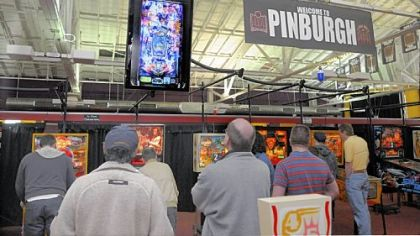 Visitors watch a video screen from a camera above one of the pinball machines. The players are practicing for the Professional & Amateur Pinball Association Pinburgh tournament in Scott. The weekend-long event is one of many regional tournaments being held throughout the country. The national championship will be held in August.