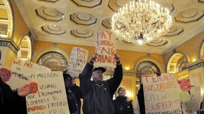 One Pittsburgh protesters chant in the lobby of the Omni William Penn during the BNY Mellon's shareholder meeting Tuesday.