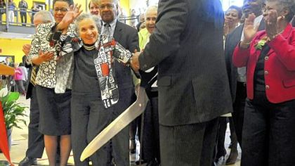 Thelma Lovette, 96, waves to the crowd after cutting the ribbon for the opening of the new Thelma Lovette YMCA in the Hill District.  Mrs. Lovette is a former resident and longtime activist in the Hill District. Her daughter, Thelma Lovette Morris, and son-in-law, Gregory Morris, are on each side of her.
