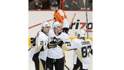 Sidney Crosby celebrates with teammates Matt Niskanen, far left, and Chris Kunitz, center.