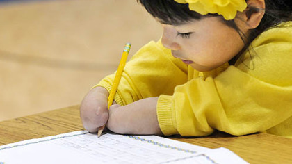 Annie Clark, a first-grade student at Wilson Christian Academy in West Mifflin who won a handwriting excellence award, demonstrates her prowess with a pencil.