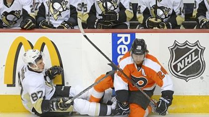 The Flyers' Claude Giroux, right, knocks Sidney Crosby off his feet seconds after the opening faceoff of Game 6 Sunday at Wells Fargo Center in Philadelphia. Giroux scored a goal moments later -- 32 seconds into the game -- and the Flyers won, 5-1, to eliminate the Penguins.