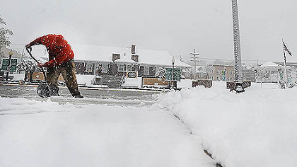A man shovels wet, heavy snow in Windber, Somerset County, today as a spring storm dumped snow and rain across the northeast.