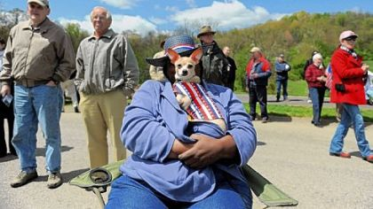 Ilene Hightower of Penn Hills holds her chihuahua, BonBon, while listening to a speaker at the Tea Party Express &quot;Restoring the American Dream&quot; tour stop at North Boundary Park in Cranberry on Friday.