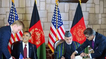President Barack Obama and Afghan President Hamid Karzai, second from right, sign a strategic partnership agreement Tuesday at the presidential palace in Kabul.