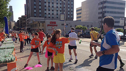 Volunteers hand out water to marathon runners along Forbes Ave.