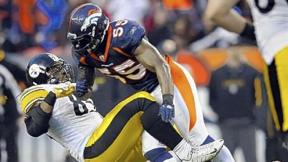 The Broncos' D.J. Williams takes down David Johnson Sunday in the third quarter.