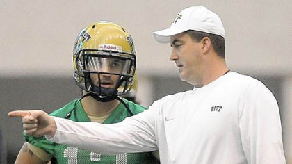 New Pitt football coach Paul Chryst, right, works with Tino Sunseri on the first day of spring practice Thursday.