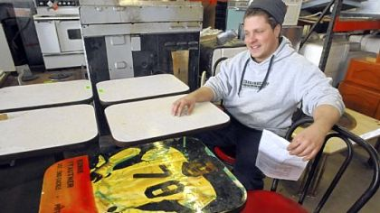 Construction Junction's Ben Lloyd with tables removed from a Downtown fast food restaurant. Some of the tabletops were decorated with pictures of famous Steelers players; the only decorated table remaining features Ernie Stautner.