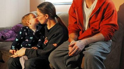 Melissa Watkins kisses her 17-month-old daughter, Steffany, while sitting with her fiance, Trevor Miles, for a television interview at their home in Beltzhoover on Friday.  Ms. Watkins is one of four women who has told police that Officer Adam Skweres offered to grant them legal favors in exchange for sexual acts.