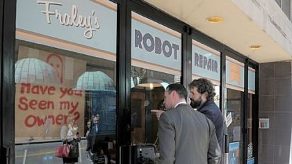 Mayor Luke Ravenstahl looks into the storefront window of Fraley's Robot Repair with artist Toby Fraley.