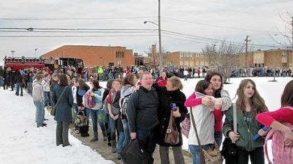Chardon High School students file out of the school, at rear, for pickup by their parents after Monday's shooting in Chardon, Ohio.