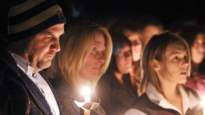 Michael Schaab's family attends a vigil marking his killing. From left are his father, Harry, his mother, Mary, and his fiancee, Megan Shively.