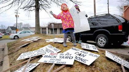 Gretta Boerner, 6, of New Wilmington, asks protesters gathered to pick up signs during the Rex Energy protest.