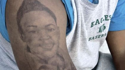Jamil Pollard shows the tattoo of his slain sister, A'aliah Scott, on his arm. An image of his second sister, India Duncan, is on his other arm.