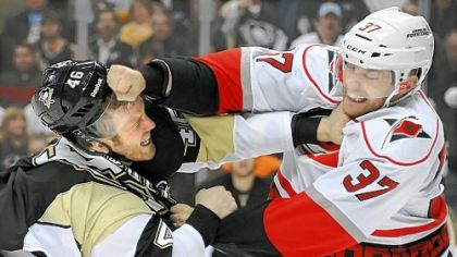Joe Vitale, left, takes a right from Carolina's Tim Brent in the third period Tuesday at Consol Energy Center.