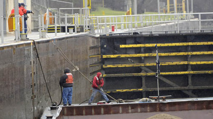 In a driving rainstorm, deckhands on the Consol Energy towboat Aliquippa fasten their barges inside Lock 4 at Charleroi on the Monongahela River and head for Monessen with two jumbo barges of sand.