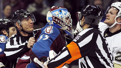 Avalanche goalie Jean-Sebastien Giguere is restrained from going after Matt Cooke, right, in the second period Saturday night in Denver. A penalty was called on Giguere for striking Cooke on the play.