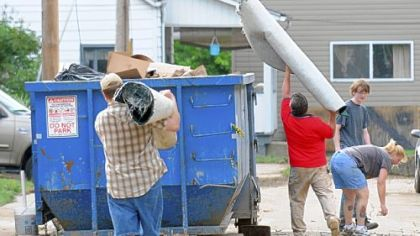 Carnegie residents parade to dumpsters with goods from their flood-damaged basements.
