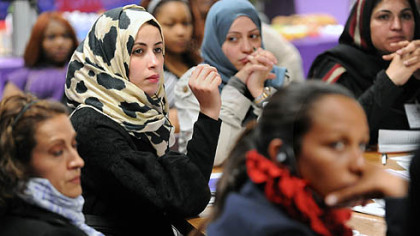 Hana Elhebshi of Libya, center in the printed scarf, asks a question during a talk and reception for awardees at Gwen's Girls in Point Breeze.