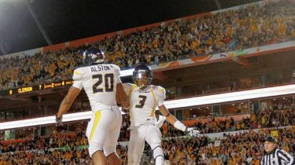 Shawne Alston, left, and Stedman Bailey celebrate Alston's 4-yard touchdown run in the Mountaineers' record-setting first half Wednesday night in Miami Gardens, Fla.