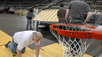 Mike Krause of Spaulding Athletic takes measurements in the key as workers at Consol Energy Center place the basketball floor for this weekend's NCAA men's basketball tournament.