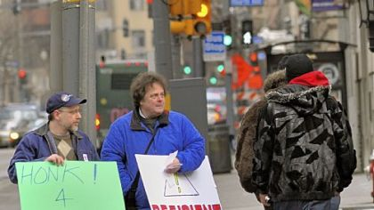 Dave Ninehouser, left, and Henry Lipput pass out literature on Wood Street, Downtown, during a demonstration organized by PA Wants to Work outside Point Park University's Lawrence Hall, where the House Democratic Policy Committee was to hold a heariing about transportation and infrastructure.
