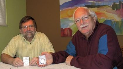 Dale Abel, left, and Richard Gaetano show coins that were encapsulated and graded by a grading service.