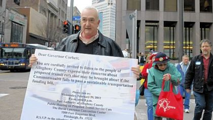 AFL-CIO spokesman Marty Marks, left, leads a group of protesters to Gov. Tom Corbett's local office Downtown on Wednesday.