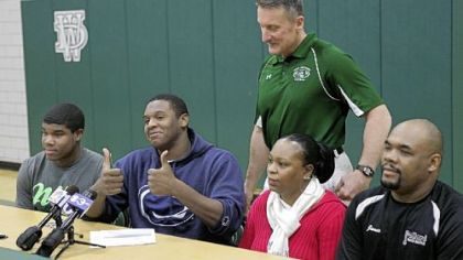 Jamil Pollard gives the thumbs up after signing with Penn State Feb. 1. With him are his parents, Lucille Bevans and James Pollard, at right, Mr. Pollard's son, Brandon Holmes, left, his coach, Clyde Folsom, standing.
