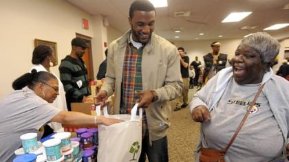 Steelers&#039; defensive back Ryan Mundy helps Nan Strong (right) gather her Thanksgiving meal fixings at the Dignity & Respect Campaign to  distribute Thanksgiving foods at the Rankin Christian Center in November. Mundy was joined by teammate Charlie Batch and other volunteers to distribute turkey, yams, corn, green beans, cranberry sauce, stuffing and dessert.