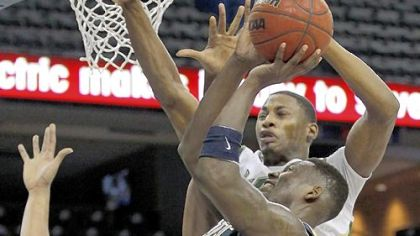 South Florida guard Hugh Robertson blocks Talib Zanna's shot in the second half Wednesday in Pitt's loss.