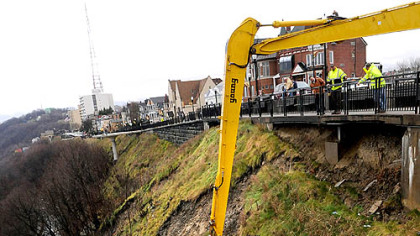 A City of Pittsburgh Public Works crew pushes part of the hillside down onto McArdle Roadway. Grandview Avenue in Mount Washington also is closed during the work.