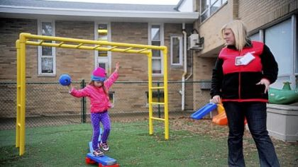 A 4-year-old walks along a balance beam while being supervised by Taryn Revak during playtime at ABC's for Children day care in Scott.