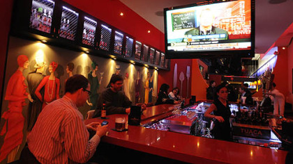 Taste of Dahntahn on Liberty Avenue features a large square bar, surrounded by high-backed red-and-white leather stools. The dining room (behind the bar) is narrow with booths along one side and tables and chairs on the other.