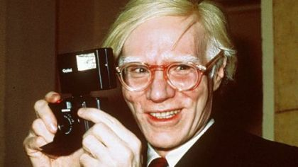 Andy Warhol holds a camera in New York in 1976.