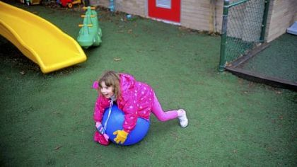 Another 4-year-old child rolls over an exercise ball. The day care center sets aside time for physical play every two hours.