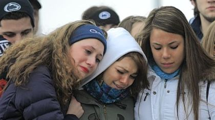 From left, Annelise Gaus of Wexford, Meredith Moore of Doylestown, Pa., and Tanya Cuadra of Rockville, Md., comfort each other Sunday at a memorial for coach Joe Paterno at his statue outside Beaver Stadium. The young women, who sung the alma mater at the memorial, are part of the Penn State Singing Lions.