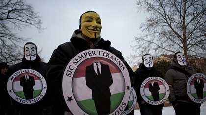 Masked protesters held the logos of the international computer hacker group Anonymous during a demonstration Feb. 11 in Budapest, Hungary. The hacker community was rocked by the news yesterday that one of the world's most-wanted computer vandals has been an FBI informant for months.