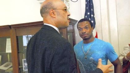 Jordan Miles, right, who was beaten by three Pittsburgh police officers, talks with city Councilman Ricky Burgess in 2011.