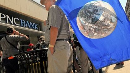 John Haer of the East End holds a flag with the Earth on it as part of a rally with the Earth Quaker Action Team. The group was protesting PNC&#039;s financing of mountaintop removal mining.