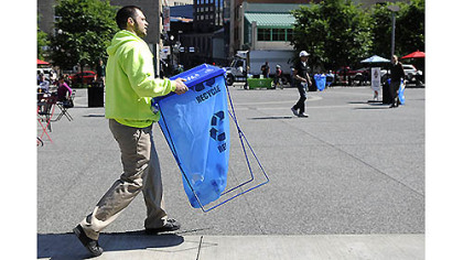 "City of Pittsburgh environmental services worker Joseph Cirigliano sets up a trashcan yesterday in Market Square before Mayor Luke Ravenstahl's announcement of the ""Don't Trash My Turf!"" campaign."