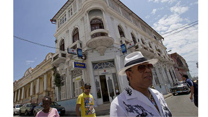 Folks walk past Norma Arias Puente's Casa Catedral on the square in Santiago de Cuba.