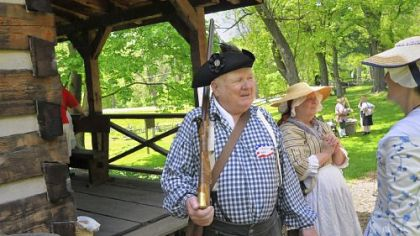 Art Farley, left, portrays James Kiddoo, who owned the grist mill down the road from the Oliver Miller Homestead in South Park. He is standing next to a standard settler's cabin.