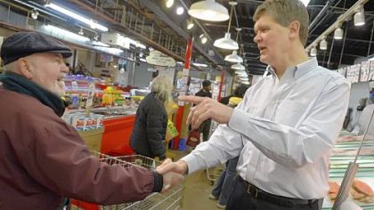 Jim Wholey, right, greets a customer at Wholey's in the Strip District. Jim Wholey is one of four brothers who operate the business, which is celebrating its 100th anniversary.
